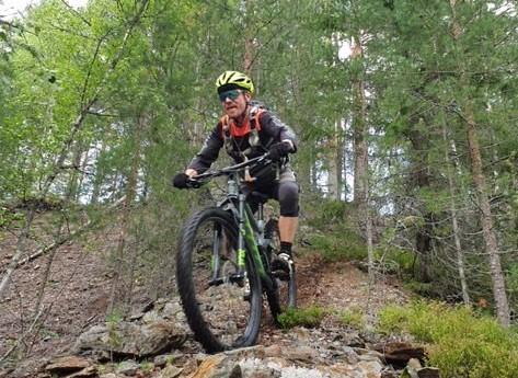 Terrengsyklist sett litt nedenifra syklende nedover en bakke med steiner og grus. (Foto: Joar Sørvik Solem)