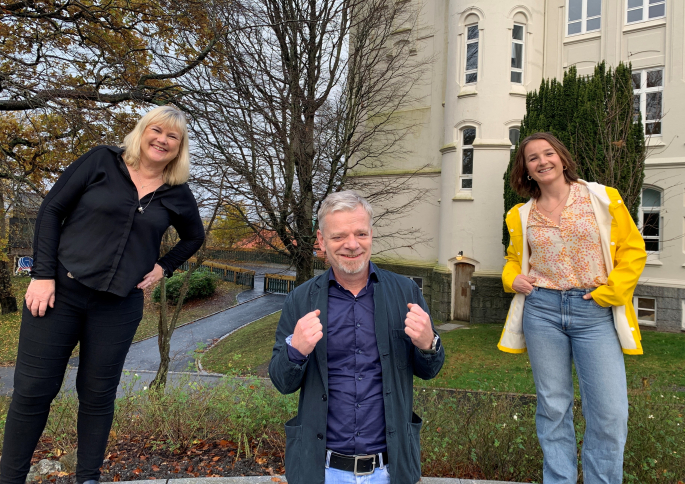 Tre smilende personer utenfor skolebygg.