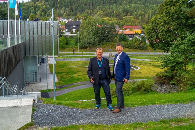 To smilende menn i dressjakke sett litt ovenfra foran skolemiljø