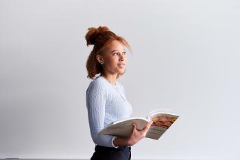 Kvinner holder en rapport, ser ut av bildet og smiler.