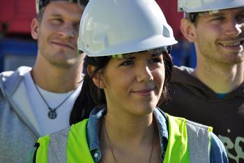 Tre smilende ungdommer med hjelm og arbeidsantrekk.