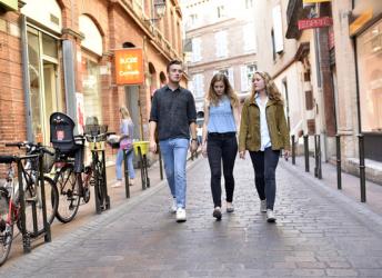 Tre ungdommer går nedover en gate