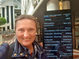 Smilende kvinne utenfor kontorbygg i Stockholm