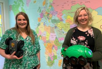 To kvinner står foran et verdenskart og holder to roboter.