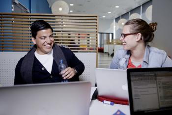 Mann og kvinne sitter rundt et bord med PCer og prater
