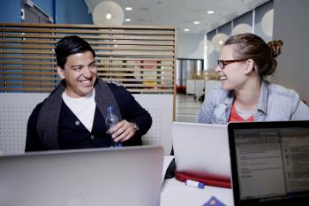 To studenter som ler og ser på hverandre.