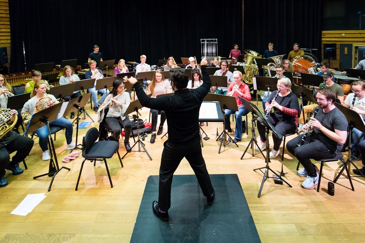 Dirigent i sorte klær står foran et orkester.