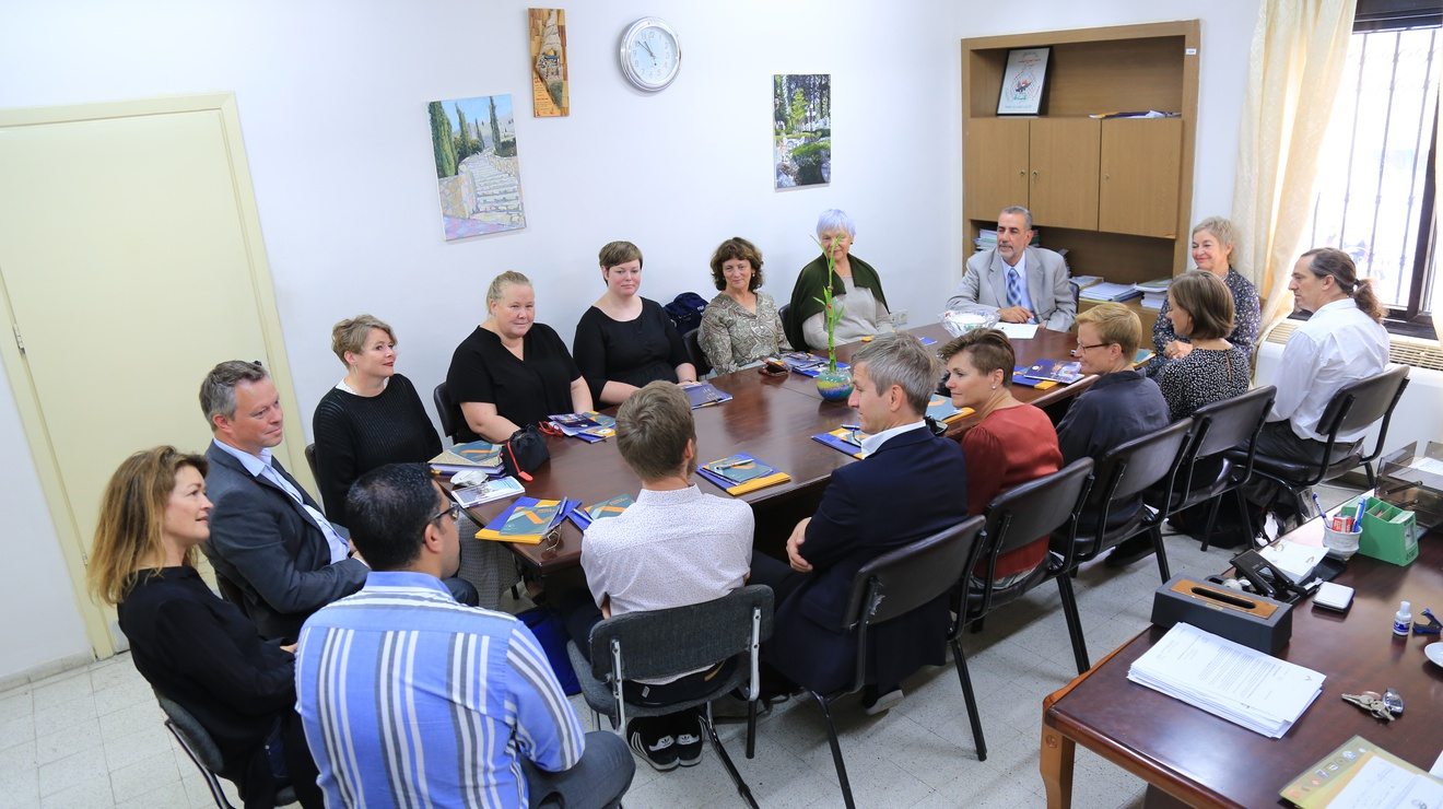 En gruppe mennesker sitter rundt et ovalt bord.